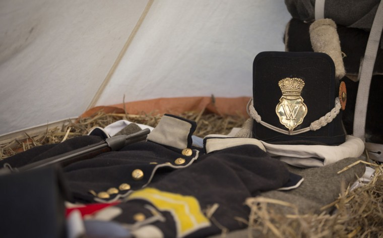 In this May 9, 2015, photo, a replica uniform and cap of the Belgian-Dutch 7th Battalion of the Line are laid out on a straw mattress inside a tent at a Napoleonic era living history camp in Elewijt, Belgium. The Belgian-Dutch living history group is coordinating their group for participation in the 200th anniversary of the Battle of Waterloo which will take place in June 2015. (AP Photo/Virginia Mayo)