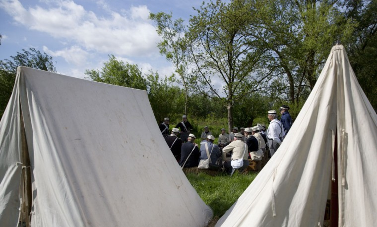 In this May 9, 2015, photo, historical re-enactors dressed as soldiers of the Belgian-Dutch 7th Battalion of the Line listen to instruction near their tents at a Napoleonic era living history camp in Elewijt, Belgium. As preparation for the 200th anniversary of the Battle of Waterloo which will take place in June 2015 members of the group will practice their battlefield tactics as well as learn various historical aspects of the battle.(AP Photo/Virginia Mayo)