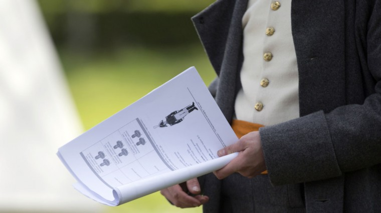 In this May 9, 2015, photo, an historical re-enactor dressed as a Lieutenant of the Belgian-Dutch 7th Battalion of the Line gives instruction on how to recognize officer insignia at a Napoleonic era living history camp in Elewijt, Belgium. As preparation for the 200th anniversary of the Battle of Waterloo which will take place in June 2015 members of the group will practice their battlefield tactics as well as learn various historical aspects of the battle. (AP Photo/Virginia Mayo)