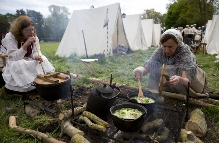 In this May 9, 2015, photo, two women, dressed in Napoleonic era dress, cook a lunchtime soup for re-enactors of the 7th Battalion of the Line at a Napoleonic era living history camp in Elewijt, Belgium. (AP Photo/Virginia Mayo)
