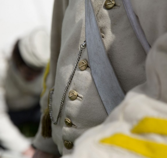 In this May 9, 2015, photo, an historical re-enactor, dressed as a soldier of the Belgian-Dutch 7th Battalion of the Line, listens to instruction at a Napoleonic era living history camp in Elewijt, Belgium. Members of the Battle of Waterloo living history group spend more than 1500 euros each on replica uniforms, ordering their cloth from a source in the United Kingdom and hiring local seamstresses to follow a period pattern. (AP Photo/Virginia Mayo)