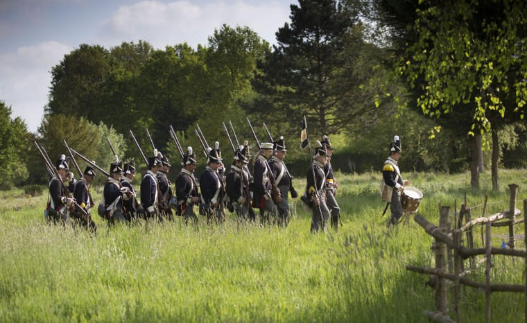 In this May 10, 2015, photo, historical re-enactors dressed as soldiers of the Belgian-Dutch 7th Battalion of the Line march in formation at a Napoleonic era living history camp in Elewijt, Belgium. The Belgian-Dutch living history group is coordinating their group for participation in the 200th anniversary of the Battle of Waterloo which will take place in June 2015. (AP Photo/Virginia Mayo)