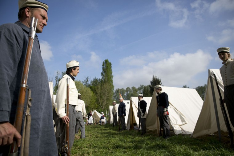 In this May 10, 2015, photo, historical re-enactors dressed as soldiers of the Belgian-Dutch 7th Battalion of the Line line up for inspection next to their tents at a Napoleonic era living history camp in Elewijt, Belgium. The Belgian-Dutch living history group is coordinating their group for participation in the 200th anniversary of the Battle of Waterloo which will take place in June 2015. (AP Photo/Virginia Mayo)