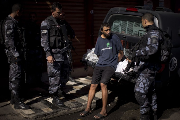 "Police officers talk to a suspect drug trafficker and bags of drugs seized during a police operation at the Mare slum complex in Rio de Janeiro, Brazil, Tuesday, June 30, 2015. The last soldiers and marines occupying the Mare complex of slums will be replaced by police as part of the program to ""pacify"" and reduce violence in the favela. The process started in April with a June 30 deadline for the army to vacate the neighborhood. (AP Photo/Felipe Dana)"