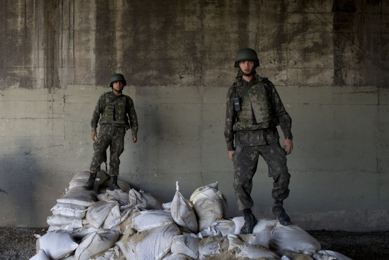 "Brazilian Army soldiers stand atop sand bags during the dismantling their base at the Mare slum complex in Rio de Janeiro, Brazil, Tuesday, June 30, 2015. The last soldiers and marines occupying the Mare complex of slums will be replaced by police as part of the program to ""pacify"" and reduce violence in the favela. The process started in April with a June 30 deadline for the army to vacate the neighborhood. (AP Photo/Felipe Dana)"