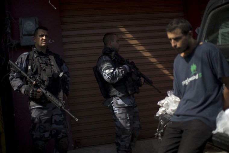 "Police officers stand next to a suspect drug trafficker and bags of drugs seized during a police operation at the Mare slum complex in Rio de Janeiro, Brazil, Tuesday, June 30, 2015. The last soldiers and marines occupying the Mare complex of slums will be replaced by police as part of the program to ""pacify"" and reduce violence in the favela. The process started in April with a June 30 deadline for the army to vacate the neighborhood. (AP Photo/Felipe Dana)"