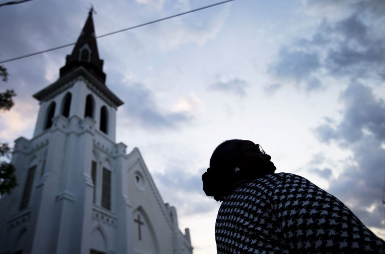 Doris Simmons, of Charleston, S.C. stands next to Emanuel AME Church, the scene of last week's mass shooting, as the sun rises Friday, June 26, 2015, in Charleston. President Barack Obama will deliver the eulogy for one of the victims, Sen. Clementa Pinckney, during his funeral Friday at a nearby college arena. (AP Photo/David Goldman)