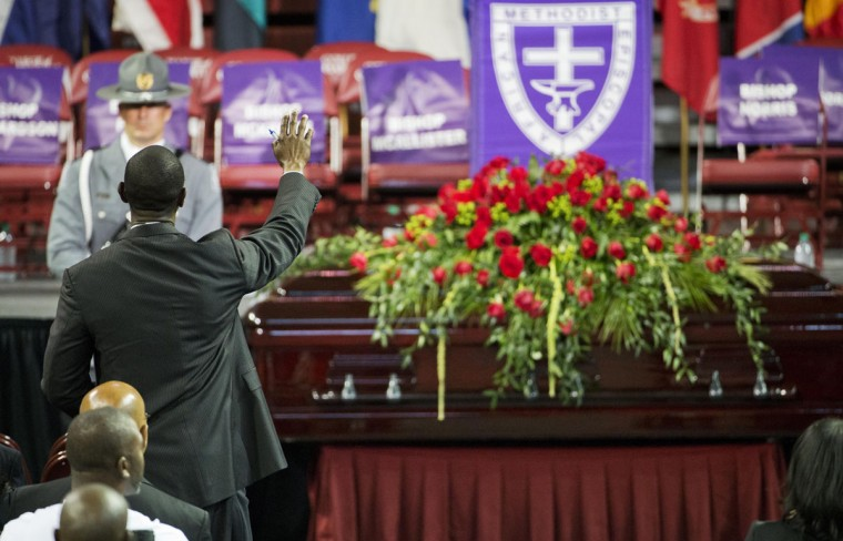 A mourner prays next to the casket of Sen. Clementa Pinckney during his funeral service, Friday, June 26, 2015, in Charleston, S.C. President Barack Obama will deliver the eulogy at Pinckney's funeral Friday at College of Charleston's TD Arena near the Emanuel AME Church, the scene of last week's shooting. (AP Photo/David Goldman)