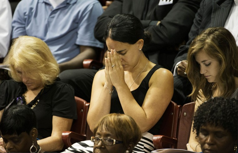 A mourner prays during the funeral service for Sen. Clementa Pinckney, Friday, June 26, 2015, in Charleston, S.C. President Barack Obama will deliver the eulogy at Pinckney's funeral Friday at a college arena near the Emanuel AME Church, the scene of last week's shooting. (AP Photo/David Goldman)