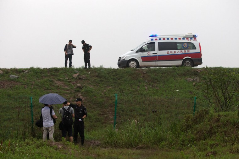 An ambulance drives past as police officers stop journalists from approaching a command center which has been set up for rescue operations of a capsized cruise ship on the Yangtze River in Jianli in central China's Hubei province, Tuesday, June 2, 2015. Divers on Tuesday pulled several survivors from inside the capsized cruise ship and searched for other survivors, state media said, giving some small hope to an apparently massive tragedy. (AP Photo/Andy Wong)