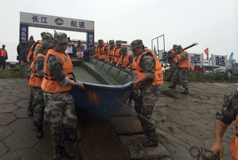 Rescue workers prepare to head out on boats on the Yangtze River to search for missing passengers after a ship capsized in central China's Hubei province Tuesday, June 2, 2015. The passenger ship carrying more than 450 people sank overnight in the Yangtze River during a storm in southern China, the official Xinhua News Agency reported Tuesday. (Chinatopix Via AP)