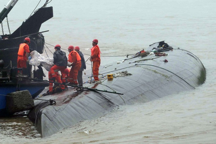 Rescue workers remove a body from the hull of a capsized ship on the Yangtze River in Jianli in central China's Hubei province, Tuesday, June 2, 2015. Divers on Tuesday pulled three people alive from inside an overturned ship and searched for other survivors, state media said, giving some small hope to an apparently massive tragedy with well over 400 people still missing on the Yangtze River. (Chinatopix Via AP)