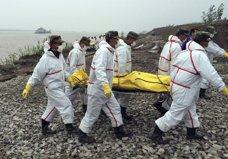 Rescue workers carry a body recovered from a capsized cruise ship in the Yangtze River in Jianli county in southern China's Hubei province Thursday, June 4, 2015. Rescuers cut three holes into the overturned hull of the river cruise ship in unsuccessful attempts to find more survivors Thursday. (Chinatopix Via AP)