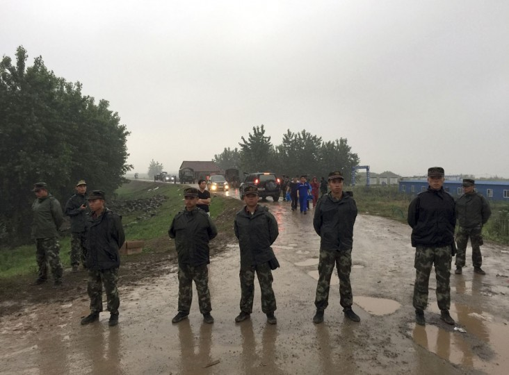 Chinese paramilitary policemen block a road leading to a command center set up for rescue operations of a capsized cruise ship on the Yangtze River in Jianli in central China's Hubei province, Tuesday, June 2, 2015. Divers on Tuesday pulled several survivors from inside the capsized cruise ship and searched for other survivors, state media said, giving some small hope to an apparently massive tragedy. (AP Photo/Andy Wong)