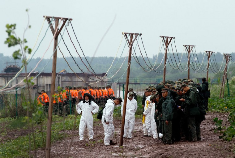 Chinese paramilitary policemen and medical officers prepare for rescue operations of a capsized cruise ship on the Yangtze River in Jianli in central China's Hubei province Wednesday, June 3, 2015. Hopes dimmed Wednesday for rescuing more than 400 people still trapped in a capsized river cruise ship that overturned in stormy weather, as hundreds of rescuers searched the Yangtze River site in what could become the deadliest Chinese maritime accident in decades. (AP Photo/Andy Wong)