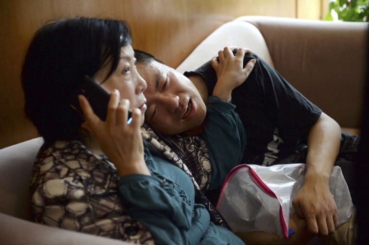 A man grieves for his missing parents as his aunt calls on her phone outside a travel agency which was involved in organizing a Yangtze River cruise, in Shanghai, China Tuesday June 2, 2015. A small cruise ship sank overnight in China's Yangtze River during a storm, state media said Tuesday. (Chinatopix via AP)