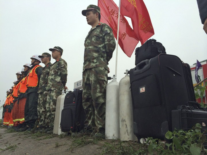 Rescue workers prepare to head out on boats on the Yangtze River to search for missing passengers after a ship capsized in central China's Hubei province Tuesday June 2, 2015. The passenger ship carrying more than 450 people sank overnight in the Yangtze River during a storm in southern China, the official Xinhua News Agency reported Tuesday. (Chinatopix Via AP)