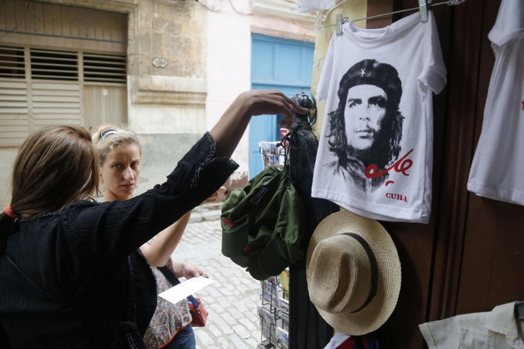 "A vendor sells Ernesto ""Che"" Guevara T-shirts and other souvenirs in Old Havana, Cuba, Monday, June 1, 2015. Travel experts and upscale magazines are urging travel to Cuba before it changes. But visitors envisioning salsa in the streets and glamorous vintage cars should also be prepared to manage without ATMs, credit cards, Wi-Fi, air-conditioning, seat belts or toilet paper. (AP Photo/Desmond Boylan)"