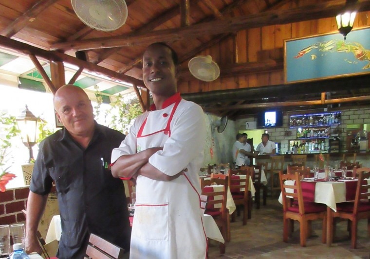 This May 14, 2015 photo shows Pedro Tejeda Torres, left, and Jonathan Nyamudihura, owner and chef at Cafe Ajiaco in Cojimar, just east of Havana, Cuba. The privately owned restaurant specializes in offering refined versions of traditional Cuban recipes. (AP Photo/Beth J. Harpaz)
