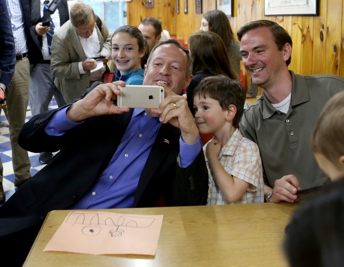 Former Maryland Gov. Martin O'Malley, left, takes a selfie with Harrison Adamec, 5, and his dad Shaun, of Framingham, Mass., during a campaign stop at Goldenrod Drive-in Restaurant, Sunday, May 31, 2015, in Manchester, N.H. O'Malley entered the Democratic presidential race on Saturday in a longshot challenge to Hillary Rodham Clinton for the 2016 nomination, casting himself as a new generation leader who would rebuild the economy and reform Wall Street. (AP Photo/Mary Schwalm)