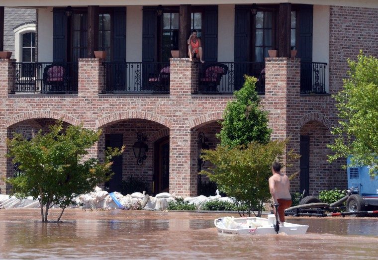 James Copeland yells out to Mindy Harvill on the second floor of her fathers home in the River Bluff subdivision in Bossier Parish, La. as he and a crew from Texas work to add sandbags to the home Saturday, June 6, 2015. (Douglas Collier/The Shreveport Times via AP)
