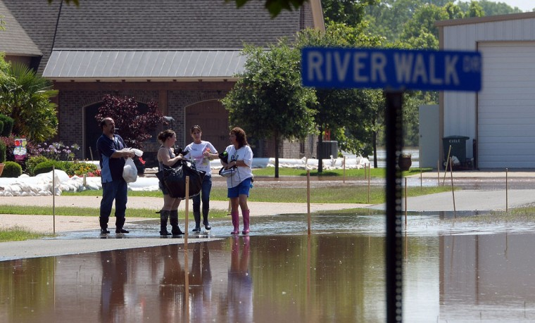 Johnny Shephard, Kristy Shephard, Barbara Shephard and Debbie Wingard pause before walking through a flooded River Walk Rd in Bossier Parish, La., Saturday, June 6, 2015, while evacuating the area from the rising waters of the Red River. (Douglas Collier/The Shreveport Times via AP)