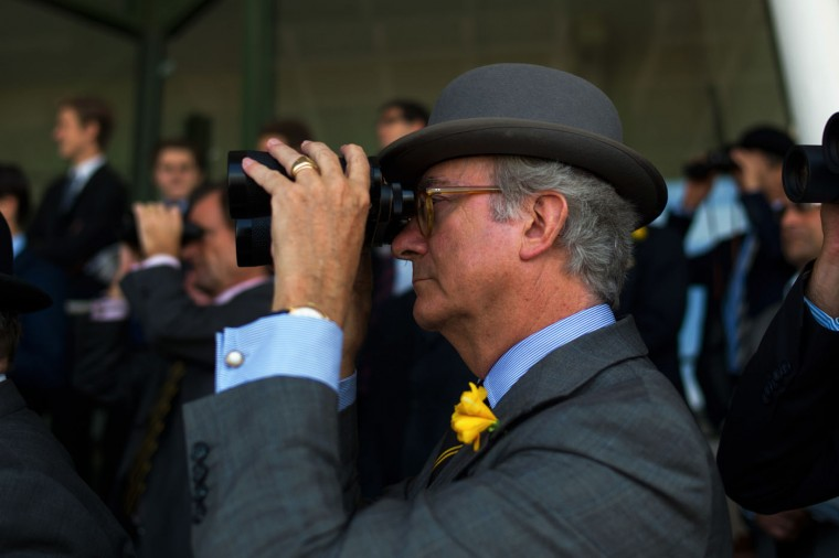 A spectator uses binoculars during the Grand Handicap horse race prior to the Prix de Diane horse race, a 2100-metre flat horse race open to fillies, in Chantilly, north of Paris, France, Sunday, June 14, 2015. (AP Photo/Thibault Camus)