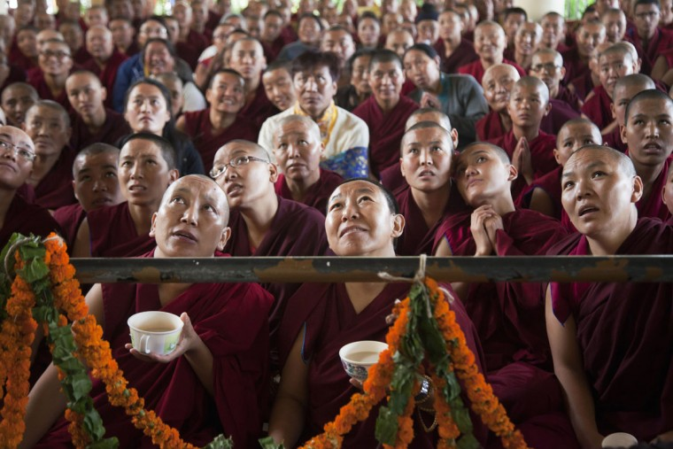 Exile Tibetan Buddhist nuns watch their spiritual leader the Dalai Lama on a TV during an official prayer ceremony to celebrate his 80th birthday in Dharmsala, India, Sunday, June 21, 2015. The Dalai Lama was born on July 6 according to the Gregorian calendar but his birthday this year falls on June 21 according to the lunar calendar followed traditionally by Tibetans. (AP Photo/Ashwini Bhatia)