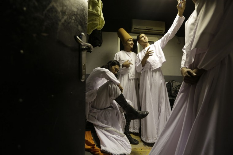 In this Thursday, April 23, 2015 photo, whirling dervishes memebers of the Al-Tannoura Egyptian Heritage Dance Troupe, take a 'selfie' in a dressing room, before their performance at the ?El Sawy culture center in Cairo, Egypt. The dancers themselves earn between 100 and 250 Egyptian pounds (between $13 and $32) per performance. But many of them describe it as far more than just a job. (AP Photo/Amr Nabil)