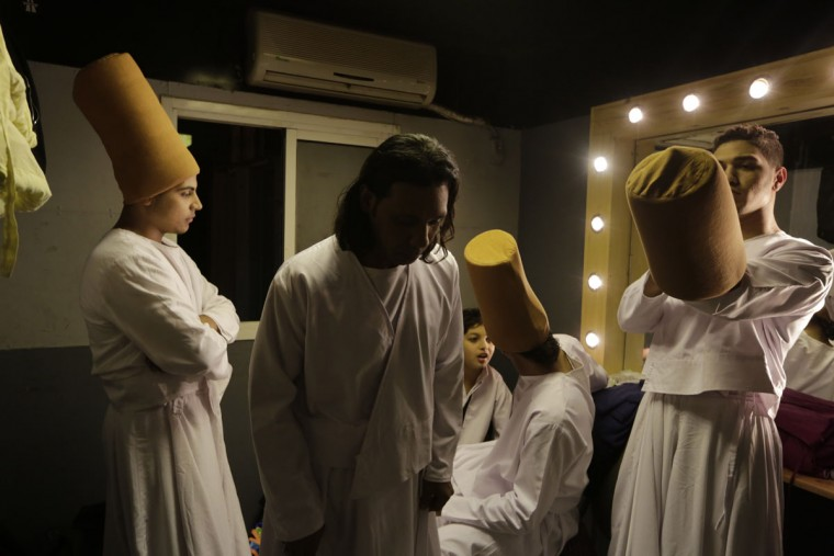 In this Thursday, April 23, 2015 photo, whirling dervish Sayed Abdel Basir, center, a member of the Al-Tannoura Egyptian Heritage Dance Troupe, prays inside a dressing room, before the group performs at the ?El Sawy cultural center in Cairo, Egypt. The dancers themselves earn between 100 and 250 Egyptian pounds (between $13 and $32) per performance. But many of them describe it as far more than just a job. (AP Photo/Amr Nabil)