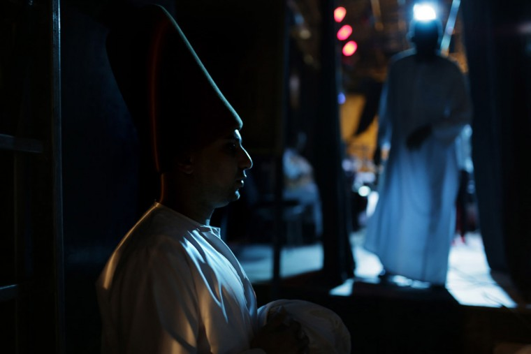 "In this Thursday, May 28, 2015 photo, whirling dervish Ali Taha, a member of the Al-Tannoura Egyptian Heritage Dance Troupe, waits backstage before a performance, at the ?El Sawy culture center in Cairo, Egypt. The dancers earn between 100 and 250 Egyptian pounds (between $13 and $32) per performance. But many of them describe it as far more than just a job. ""I'm ready to dance for free, especially with the Mawlawiyah dervishes,î said Taha. ìWhile whirling I feel like a white bird flying in the sky."" (AP Photo/Amr Nabil)"