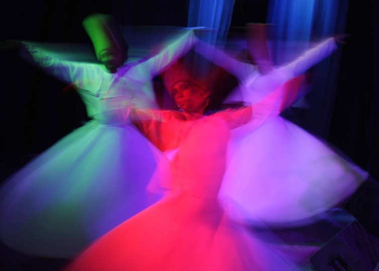 In this Thursday, April 23, 2015 photo, whirling dervish Sayed Abdel Basir, center, a member of the Al-Tannoura Egyptian Heritage Dance Troupe spins during a performance at the ?El Sawy cultural center in Cairo, Egypt. The dervishes perform across the city at cultural centers, cruise ships, hotels and weddings. The art form draws its roots from the ecstatic movements of Sufi Muslim mystics seeking a state of delirious oneness with God. (AP Photo/Amr Nabil)