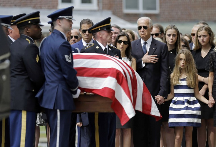 Vice President Joe Biden, accompanied by his family, holds his hand over his heart as he watches an honor guard carry a casket containing the remains of his son, former Delaware Attorney General Beau Biden, into St. Anthony of Padua Roman Catholic Church in Wilmington, Del., Saturday, June 6, 2015, for funeral services. Standing alongside the vice president are Beau's widow Hallie Biden, left, and daughter, Natalie. Beau Biden died of brain cancer May 30 at age 46. (AP Photo/Patrick Semansky)