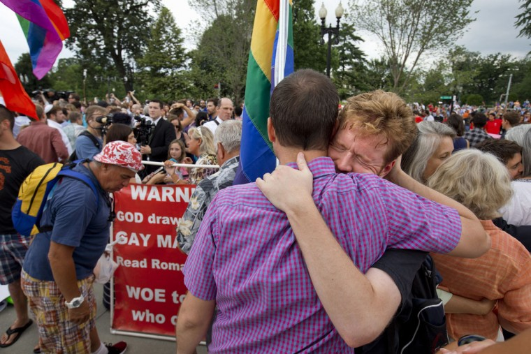 John Becker, right, hugs his friend and fellow LGBT advocate Paul Guequierre, outside the Supreme Court in Washington, Friday, June 26, 2015, after the court declared that same-sex couples have a right to marry anywhere in the US. (AP Photo/Jacquelyn Martin)