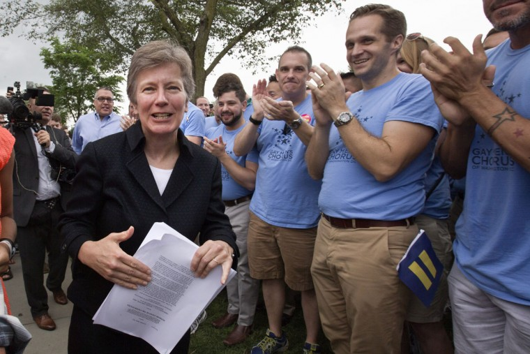 Attorney Mary Bonauto, left, is applauded by the Gay Men's Chorus of Washington in Washington, Friday, June 26, 2015, after the Supreme Court declared that same-sex couples have a right to marry anywhere in the US. (AP Photo/Jacquelyn Martin)