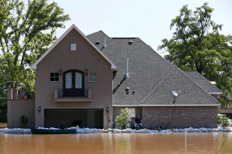 A man sits on his porch after looking for leaks in a wall of sandbags he built to protect his property from the flooding of the Red River, Thursday, June 11, 2015, in Shreveport, La. Flooding from the swelling river put hundreds of homes and farmland underwater or in danger in rural northwest Louisiana, and state officials said Thursday that they would seek a federal disaster declaration to get help for residents. (AP Photo/Jonathan Bachman)