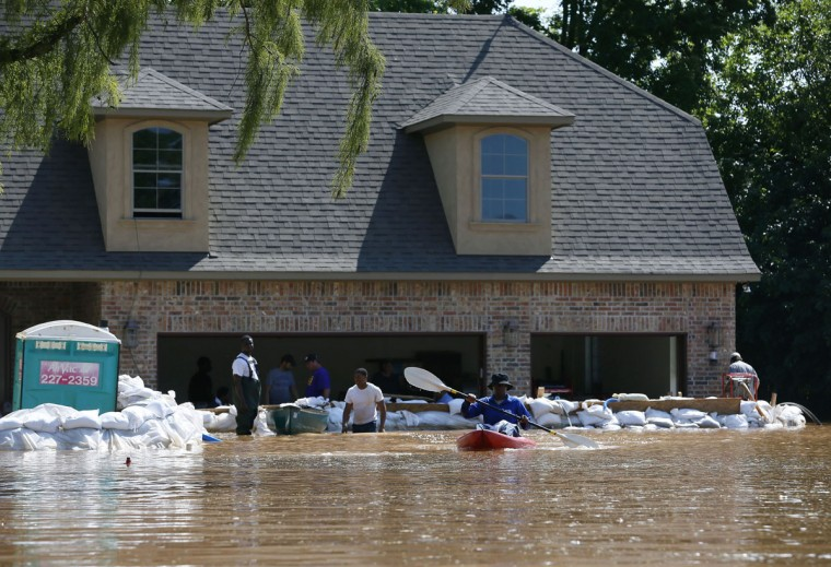 Margaret Bordley kayaks her way back to a loading site after dropping off sandbags to a home that is trying to protect itself from water caused by flooding of the Red River, Thursday, June 11, 2015, in Shreveport, La. Flooding from the swelling river put hundreds of homes and farmland underwater or in danger in rural northwest Louisiana, and state officials said Thursday that they would seek a federal disaster declaration to get help for residents. (AP Photo/Jonathan Bachman)