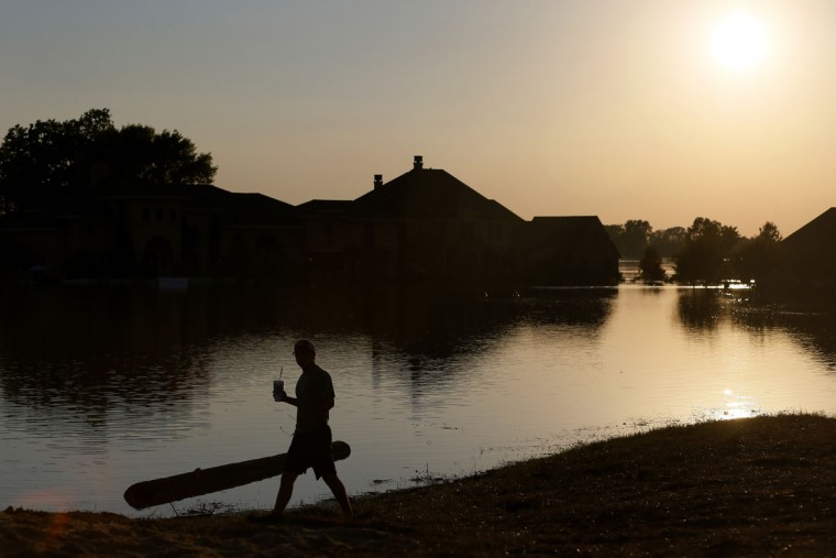 Walker Bell walks along a levee past submerged houses caused by the flooding of the Red River, Wednesday, June 10, 2015, in Bossier City, La. (AP Photo/Jonathan Bachman)