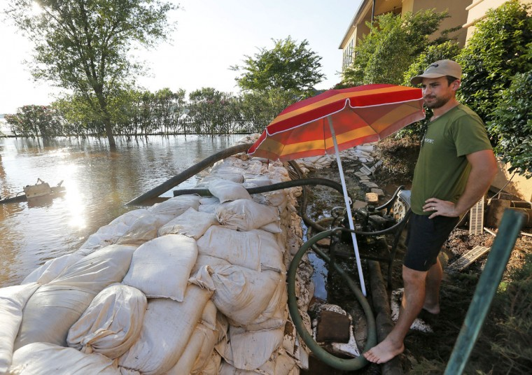 Spencer Sinclair checks on sandbags and a water pump built to protect a friend's home from water caused by the flooding of the Red River, Wednesday, June 10, 2015, in Bossier City, La. (AP Photo/Jonathan Bachman)