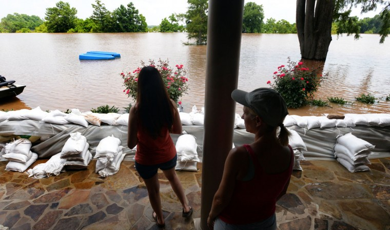 Kellie Simpson, right, and Lacie Spinks stand on their patio Monday, June 8, 2015, and look out into their backyard in the Les Maisons Sur La Rouge subdivision in Shreveport, La., where the only thing stopping water from coming into their house is the sand bag wall. (Henrietta Wildsmith/The Shreveport Times via AP)