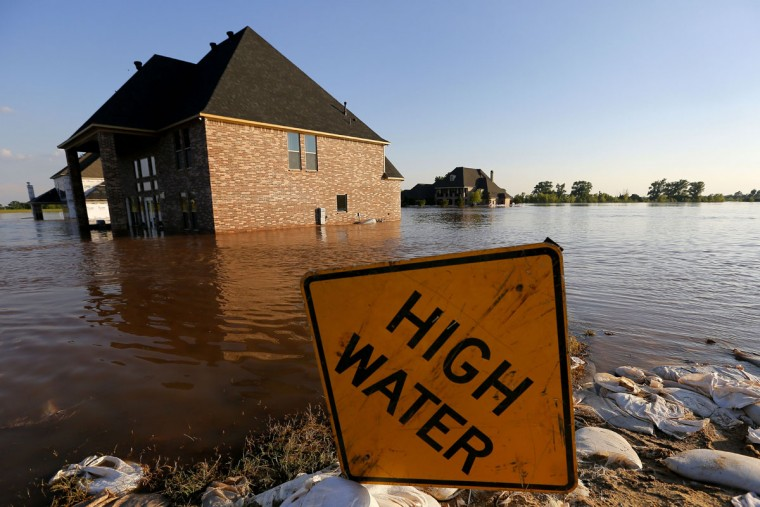 A sign is viewed near a submerged home caused by flooding from the Red River, Wednesday, June 10, 2015, in Bossier City, La. (AP Photo/Jonathan Bachman)
