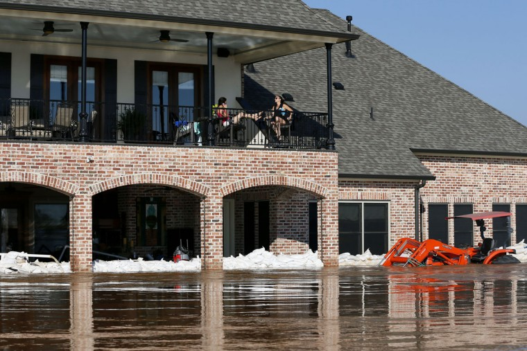 Residents sit on the balcony of their partially submerged home caused by flooding from the Red River, Wednesday, June 10, 2015, in Bossier City, La. (AP Photo/Jonathan Bachman)