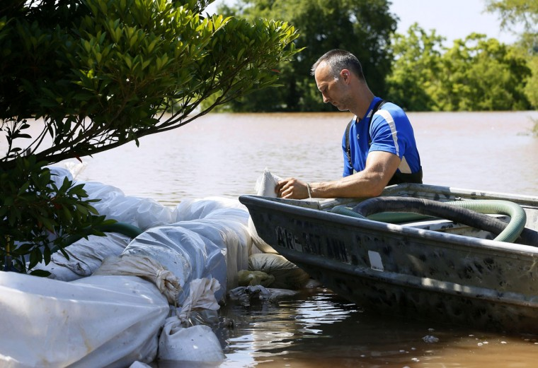 Tom Siskron III places sandbags around his property in an attempt to protect it from the flooding of the Red River, Thursday, June 11, 2015, in Shreveport, La. (AP Photo/Jonathan Bachman)