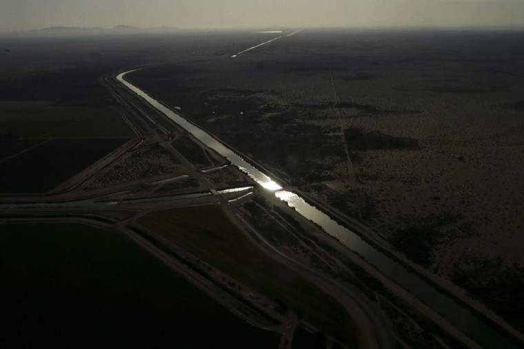 In this May 1, 2015, aerial photo, morning light reflects off water in the All-American Canal near Calexico, Calif. Colorado River water is diverted near Yuma, Arizona, to an 82-mile canal that runs west along the Mexican border and then north into 1,700 miles of gated dirt and concrete channels that crisscross farms. When gates open, water floods fields and gravity carries increasingly salty runoff downhill through the New and Alamo rivers to the Salton Sea. (AP Photo/Gregory Bull)