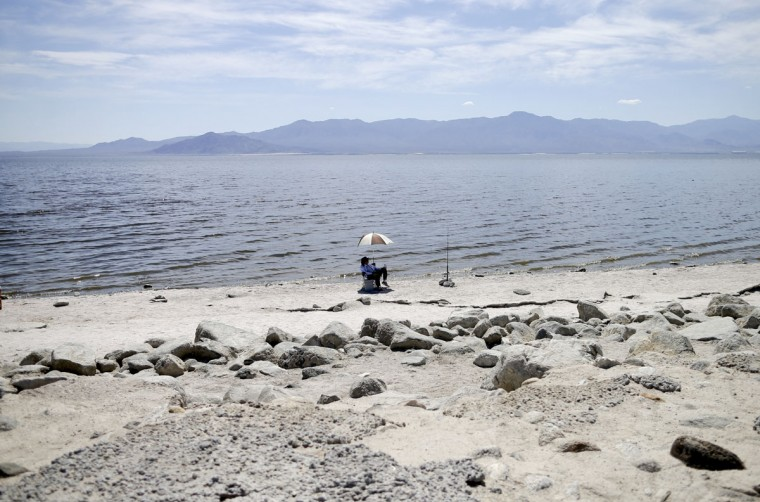 In this April 30, 2015, photo, Ed Victoria of Los Angeles sits under an umbrella as he fishes for tilapia along the receding banks of the Salton Sea near Bombay Beach, Calif. The lake is shrinking and on the verge of getting smaller as more water goes to coastal cities. (AP Photo/Gregory Bull)