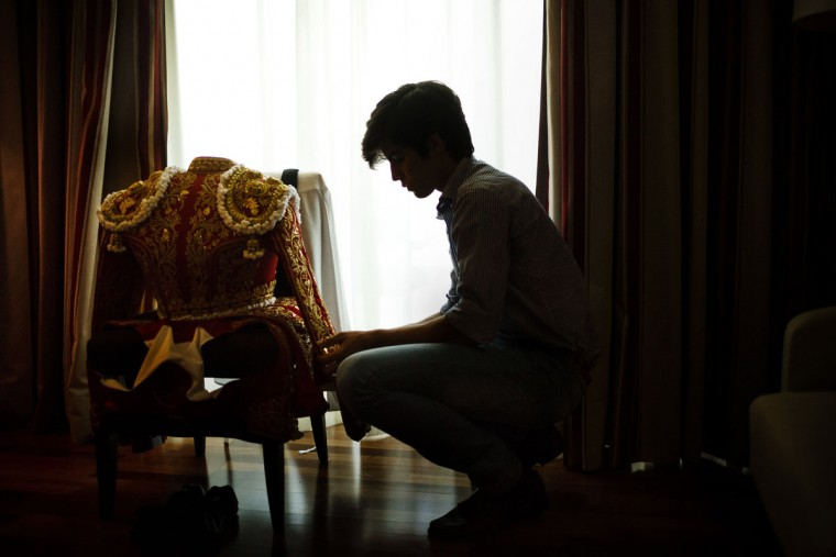 In this photo taken Saturday, May 30, 2015, Spanish bullfighter Alvaro Lorenzo's younger brother, Gonzalo Lorenzo, looks at his brother's jacket in their hotel room before a bullfight with Alcurrucen ranch fighting bulls in Aranjuez, near Madrid, Spain. Bullfighting is an ancient tradition in Spain. (AP Photo/Daniel Ochoa de Olza)