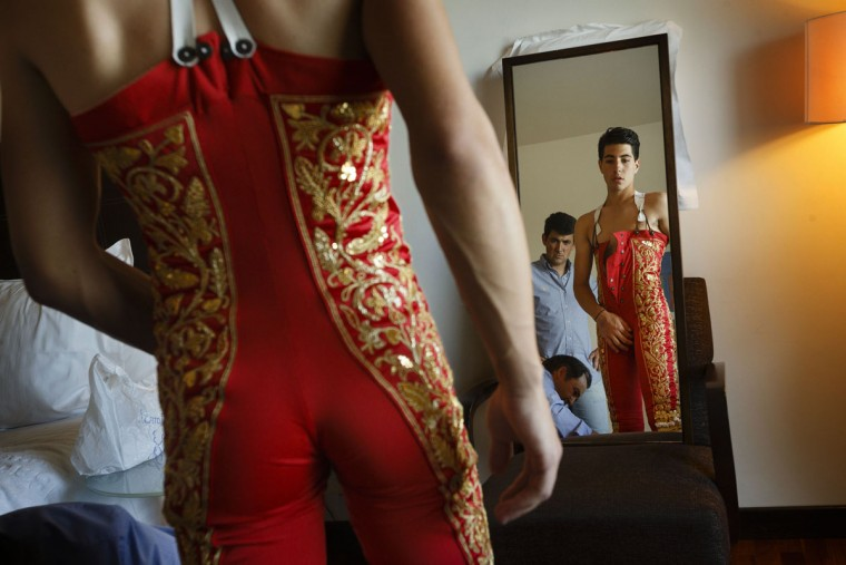 In this photo taken Saturday, May 30, 2015, Spanish bullfighter Alvaro Lorenzo looks at himself in a mirror while getting dressed for a bullfight with Alcurrucen ranch fighting bulls in Aranjuez, near Madrid, Spain. Bullfighters are usually dressed by their best men, and assistant named 'mozo de espadas', a ritual usually undertaken in silence and in a ceremonial manner. Bullfighting is an ancient tradition in Spain. (AP Photo/Daniel Ochoa de Olza)