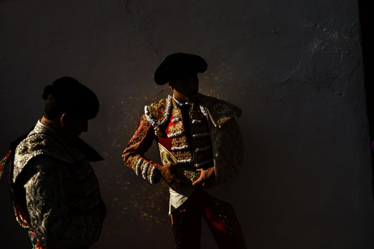 In this photo taken Saturday, May 30, 2015, Spanish bullfighter Alvaro Lorenzo's suit reflects golden spots on the wall as he waits with an assistant to do the 'paseillo' or ritual entrance to the arena before a bullfight with Alcurrucen ranch fighting bulls in Aranjuez, near Madrid, Spain. Bullfighting is an ancient tradition in Spain. (AP Photo/Daniel Ochoa de Olza)