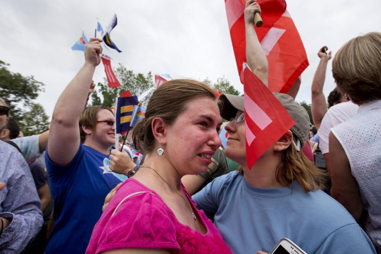 Ariel Olah of Detroit, left, and her fiancee Katie Boatman, are overcome by emotion outside the Supreme Court in Washington, Friday, June 26, 2015, as the ruling on same-sex marriage was announced. The court declared that same-sex couples have a right to marry anywhere in the US. (AP Photo/Jacquelyn Martin)