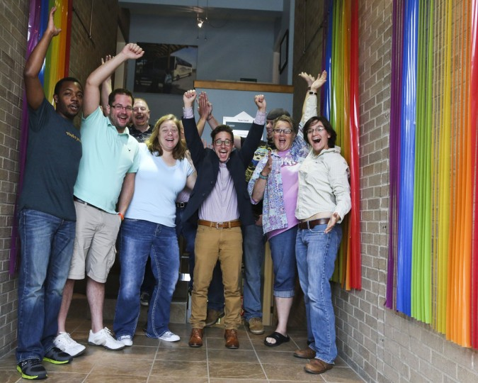 Staff from the Gay and Lesbian Resource Center celebrate after the Supreme Court ruling in favor of same sex marriage in Kalamazoo, Mich. on Friday June 26, 2015. The court's 5-4 ruling means the remaining 14 states, in the South and Midwest, will have to stop enforcing their bans on same-sex marriage. (Crystal Vander Weit/Kalamazoo Gazette-MLive Media Group via AP)
